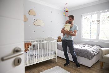 father comforting newborn baby in nursery