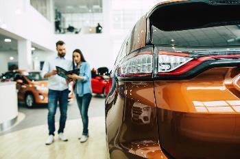 couple looking at new cars at dealership