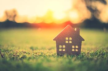 Small wooden home token sitting in grass with sunset behind