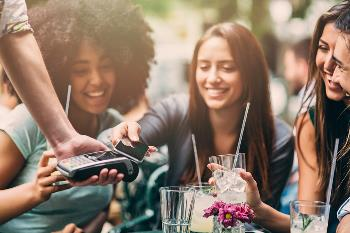 young people using cell phone to make mobile payment
